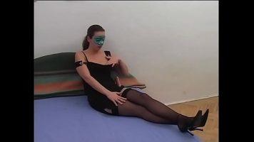 Tarfa care poarta o masca pe fata si sta dezbracata pe un pat