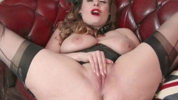 Blonda cu sanii mari sta pe canapea si se masturbeaza