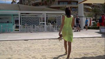 Este fara lenjerie intima pe plaja si poarta o rochie foarte transparenta