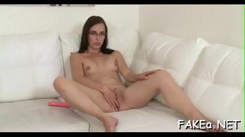 Fata care poarta ochelari sta dezbracata pe o canapea si isi atinge pasarica